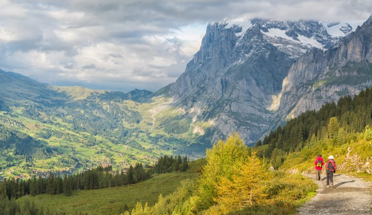 Hikers walking on spectacular mountain scenery in Switzerland
